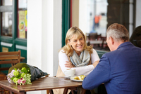 Mature couple on date chatting at sidewalk cafe table