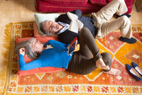 Couple reading book on floor