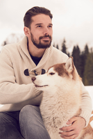 Young man petting husky in snow, Elmau, Bavaria, Germany