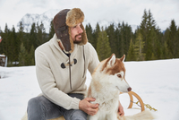 Young man wearing trapper hat petting husky in snow, Elmau, Bavaria, Germany