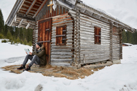 Young man reading map sitting outside log cabin in winter, Elmau, Bavaria, Germany
