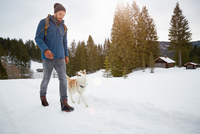 Young man walking husky in snow covered landscape, Elmau, Bavaria, Germany