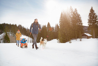 Parents pulling sons on toboggan in snow covered landscape, Elmau, Bavaria, Germany