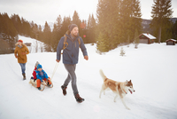 Parents with husky pulling sons on toboggan in snow covered landscape, Elmau, Bavaria, Germany