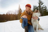 Woman sitting with husky in snow covered landscape, Elmau, Bavaria, Germany