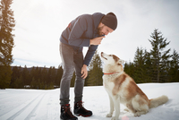 Young man training husky in snow covered landscape, Elmau, Bavaria, Germany