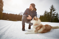 Young man crouching with husky in snow covered landscape, Elmau, Bavaria, Germany