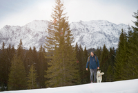 Young man walking uphill with husky in snow covered landscape, Elmau, Bavaria, Germany