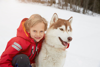 Portrait of boy and husky in snow, Elmau, Bavaria, Germany