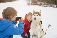 Boy taking smartphone photo of brother and husky in snow, Elmau, Bavaria, Germany