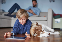 Boy lying on living room floor with husky using digital tablet