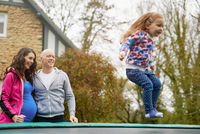 Parents watching daughter bounce on trampoline