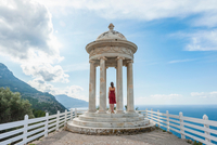 Woman wearing red dress looking out from coastal monument, Majorca, Spain