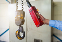 Hand of worker operating chain hoist