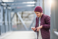 Man on bridge wearing knit hat and ear buds looking down at smartphone