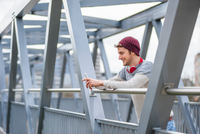 Man on bridge leaning against railings looking at smartphone smiling