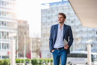 Man in city, hands in pockets, carrying digital tablet looking away smiling