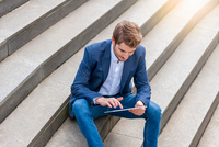 Man sitting on steps looking down using digital tablet
