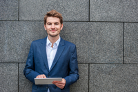 Man wearing suit jacket leaning against wall using digital tablet looking at camera smiling
