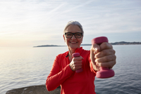 Mature woman beside water, exercising with hand weights, smiling