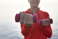 Mature woman beside water, exercising with hand weights, mid section