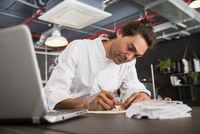 Chef in restaurant writing in notepad