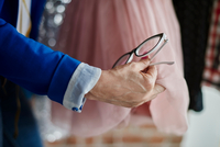 Cropped view of woman hand holding eyeglasses examining chiffon dress