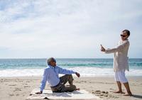 Senior couple on beach, woman taking photograph of man using smartphone 11015280504| 写真素材・ストックフォト・画像・イラスト素材|アマナイメージズ