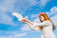 Teenage girl releasing white dove into sky