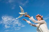 Woman releasing white dove into sky