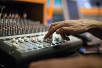 Woman using mixer desk in recording studio, focus on hand