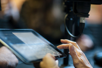 Woman using digital tablet in recording studio, close-up