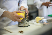 Chef grating cheese in kitchen