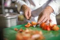 Chef slicing tomatoes on table