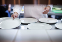 Chef laying out empty plates in kitchen