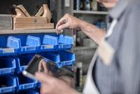 Close up of senior craftsman with digital tablet selecting components in antique restoration workshop 11015281185| 写真素材・ストックフォト・画像・イラスト素材|アマナイメージズ