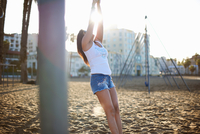 Woman on beach wearing denim shorts and vest arms raised leaning back