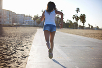 Full length rear view of woman jogging on path at beach