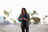Woman carrying handbag looking down at smartphone smiling