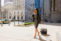 Businesswoman walking outdoors, pulling wheeled suitcase, using smartphone