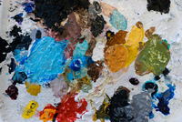 Overhead view of artist palette splodged with dried colorful paint