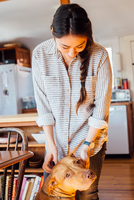 Woman in kitchen looking down stroking dog