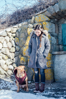 Full length view of woman with dog in front of dry stone building