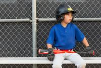Boy with baseball bat watching from bench at baseball practise