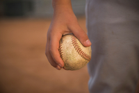 Cropped close up of boy's hand holding ball at baseball practise