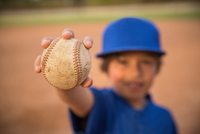 Blurred portrait of boy holding up ball at baseball practise
