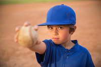 Portrait of boy holding up ball at baseball practise