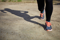 Shadow and legs of woman wearing running shoes