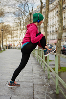 Side view of jogger stretching leg on fence