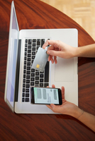 Woman with laptop holding credit card and smartphone